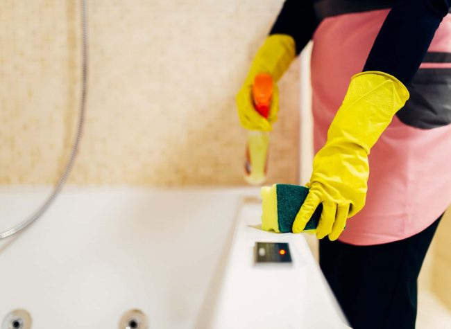 Maid cleans the bathtube with a cleaning spray